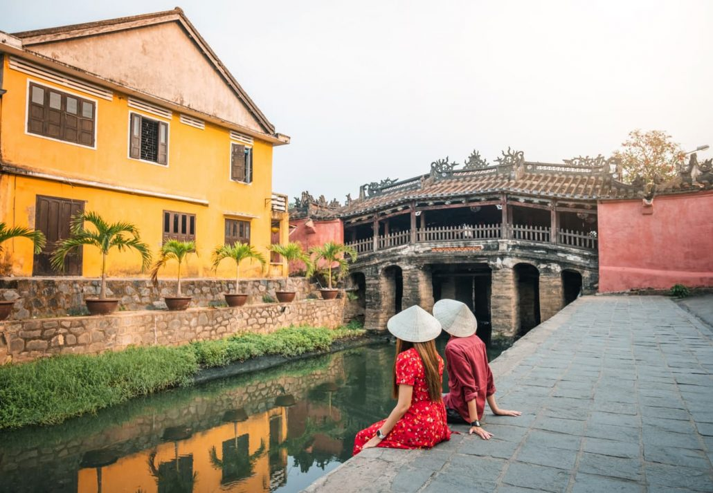 Travel couple with Japanese Covered Bridge, in Hoi An, Vietnam.