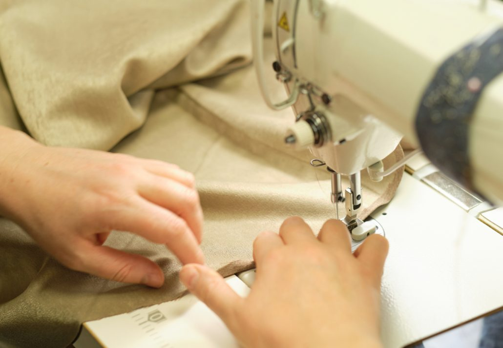 Close up view of sewing process. Female hands stitching fabric on professional manufacturing machine at workplace.