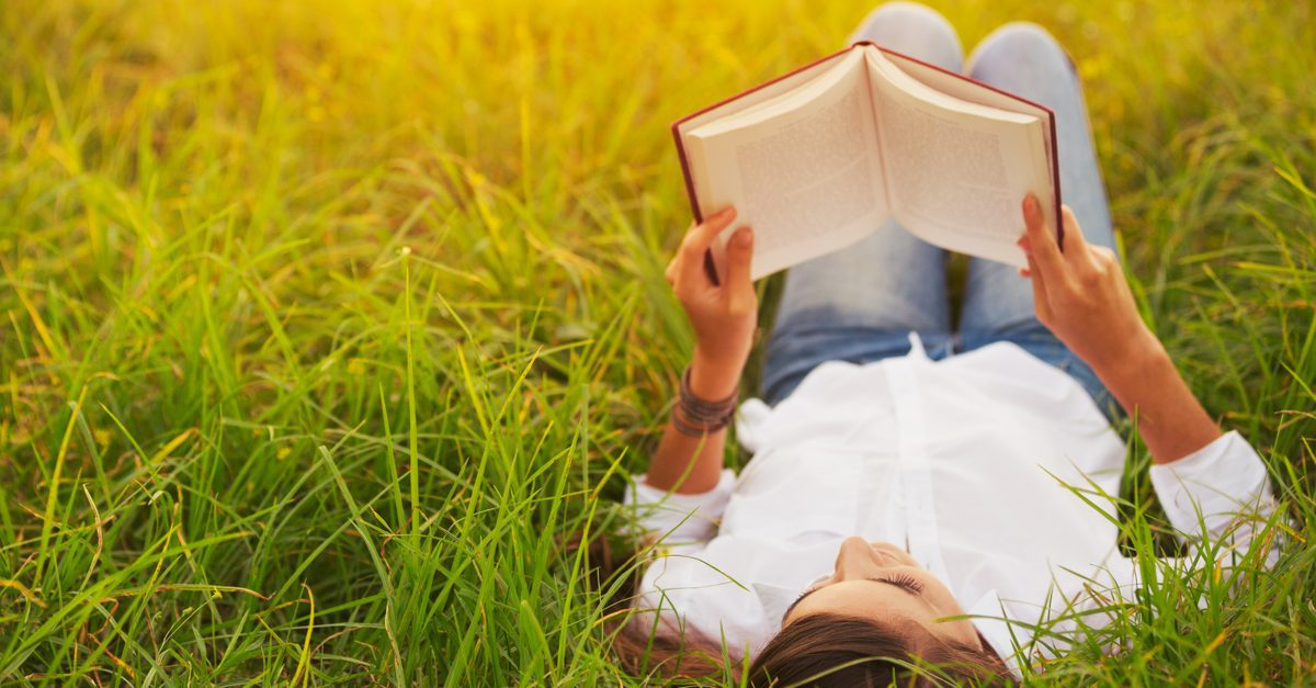 Woman lying on the grass while reading a book.