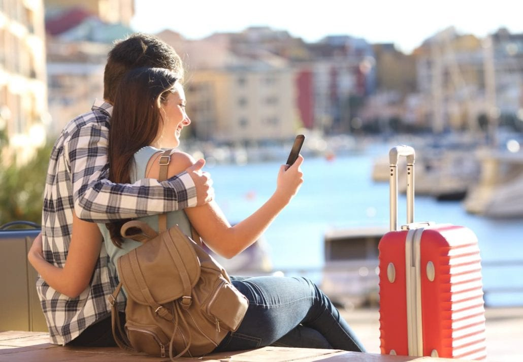 Tourist couple booking a hotel on their smartphone while traveling in Europe.