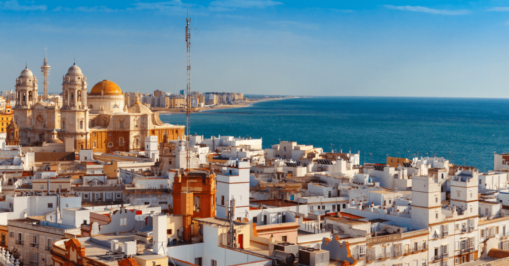 View of the historic white and orange buildings by the blue ocean in Cadiz, Spain.