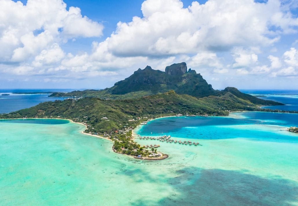 Aerial view of Matira point with overwater bungalows of a luxury resorts and Mount Otemanu with amazing divine coast and lagoon.