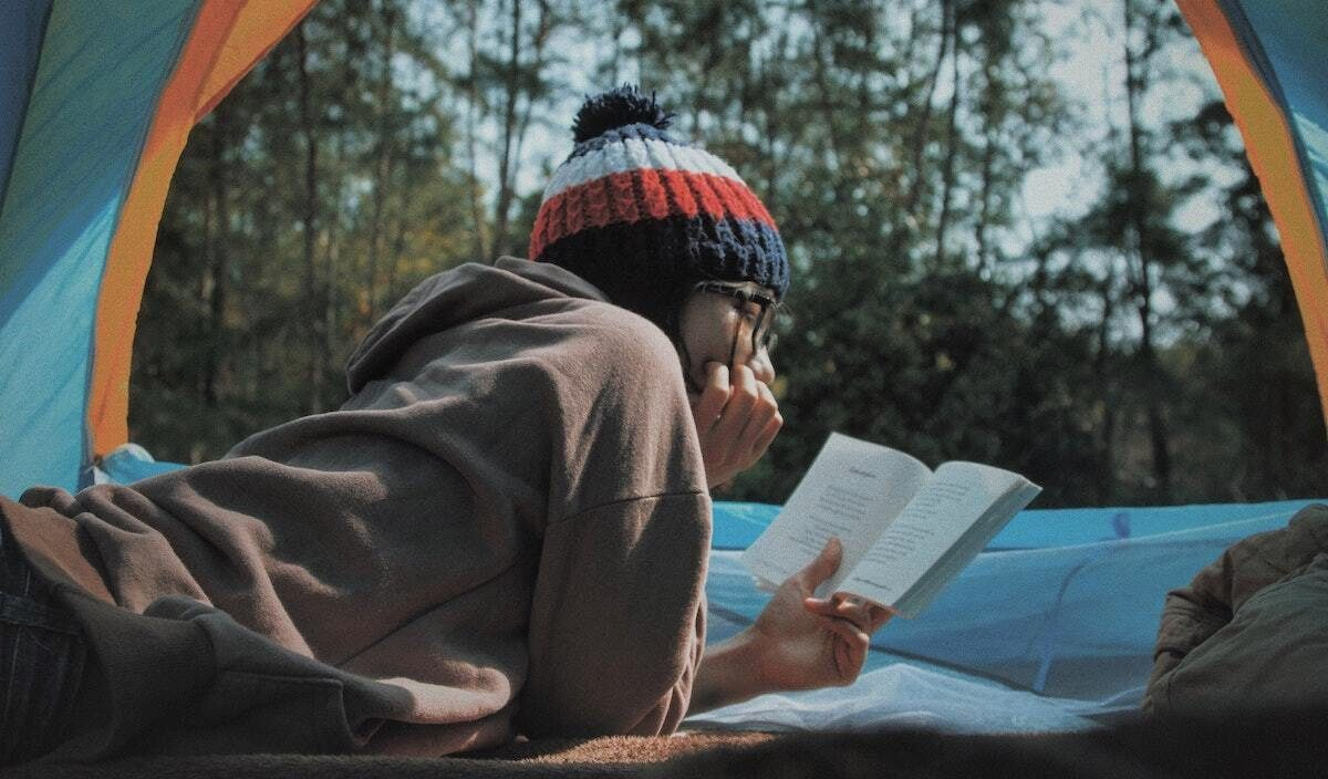girl reading while camping