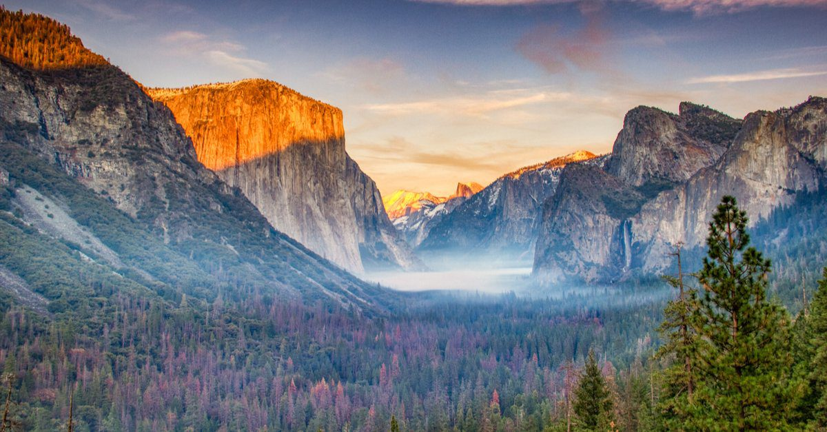 View of the Yosemite Park mountains covered in fog during the sunset.
