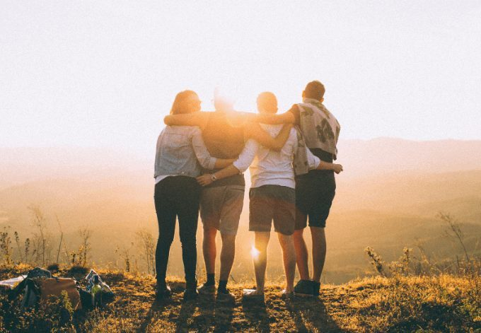 Four friends hugging each other and overlooking a natural landscape at sunset.