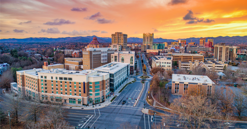 Aerial view of the buildings at Downtown Asheville surrounded by the Appalachian Mountains during a the sunset.