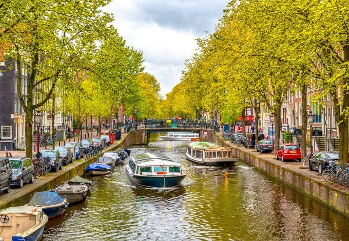 An Amsterdam Canal lined with green trees.