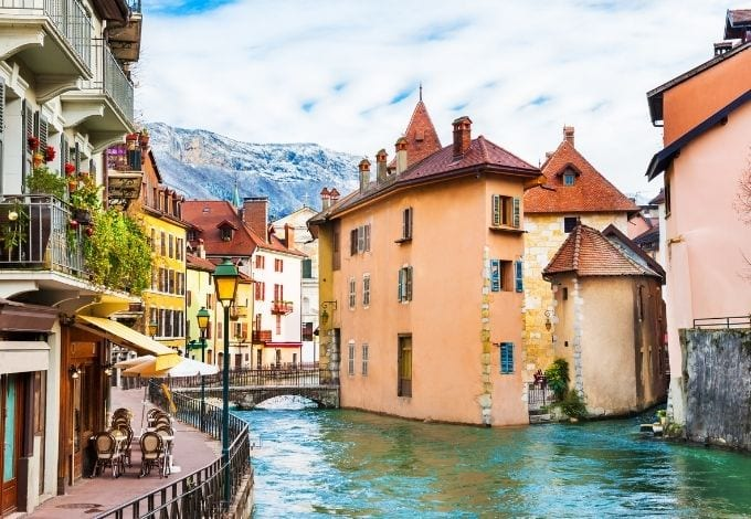 A small water canal in Annecy, France, lined with pastel-hued buildings.