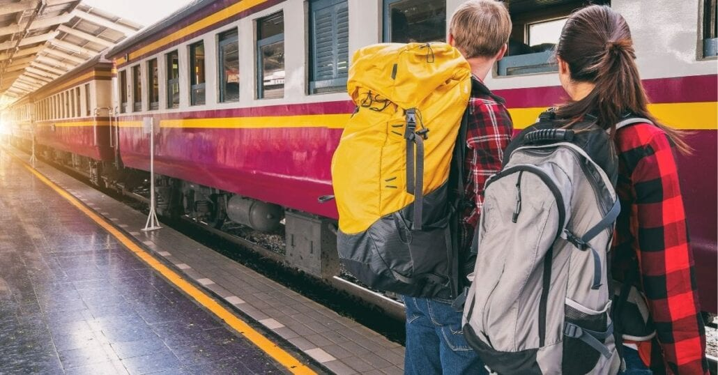 Two backpackers, a boy, and a girl, waiting for a train on the platform.