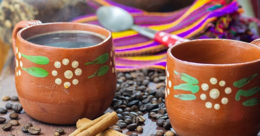A decorated earthen clay pot filled with Cafe de Olla, a typical Mexican drink.