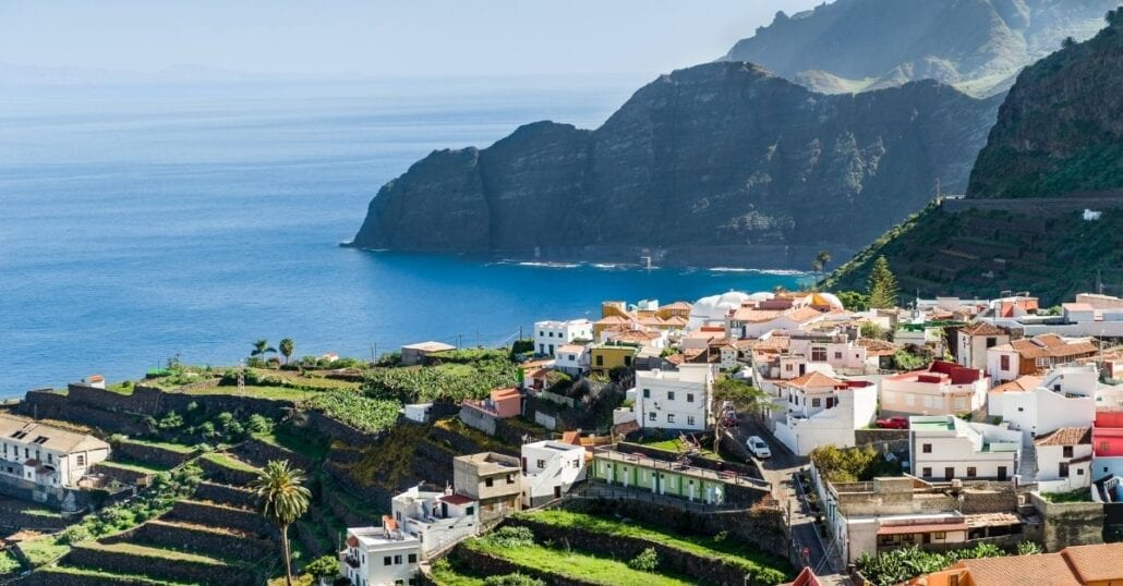 Aerial view of Canary Island's landscape with the ocean, white houses and mountains.