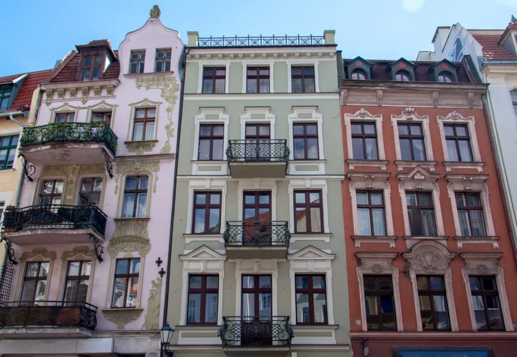 View on three antique, colourful, facades of buildings of Art Nouveau/Modern Style with balconies from the end of 19th century.