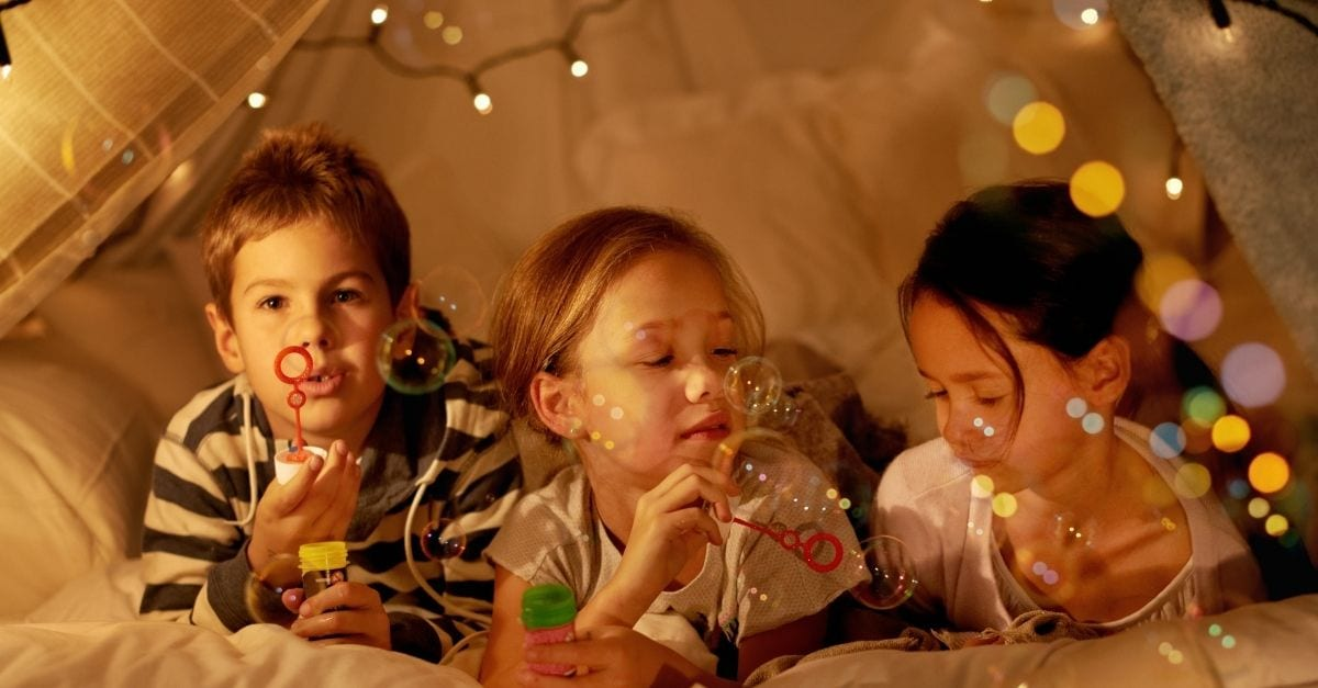 Three kids, a boy and two girls, playing at night inside a bedroom tent.