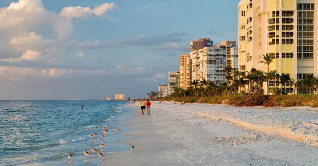 Two people walking by the ocean on a sandy beach in Naples, Florida.