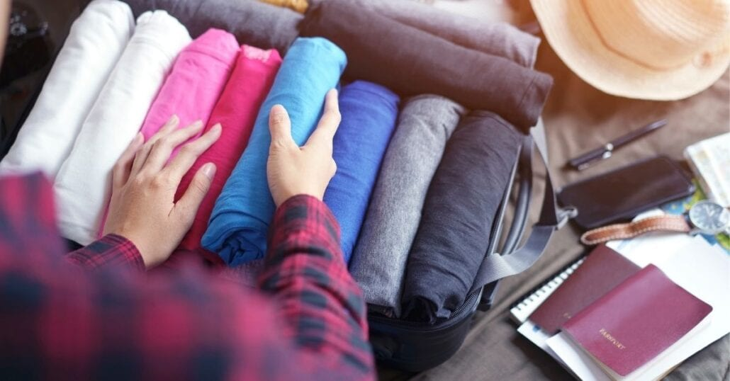 Woman organizing t-shirts on a suitcase before traveling.