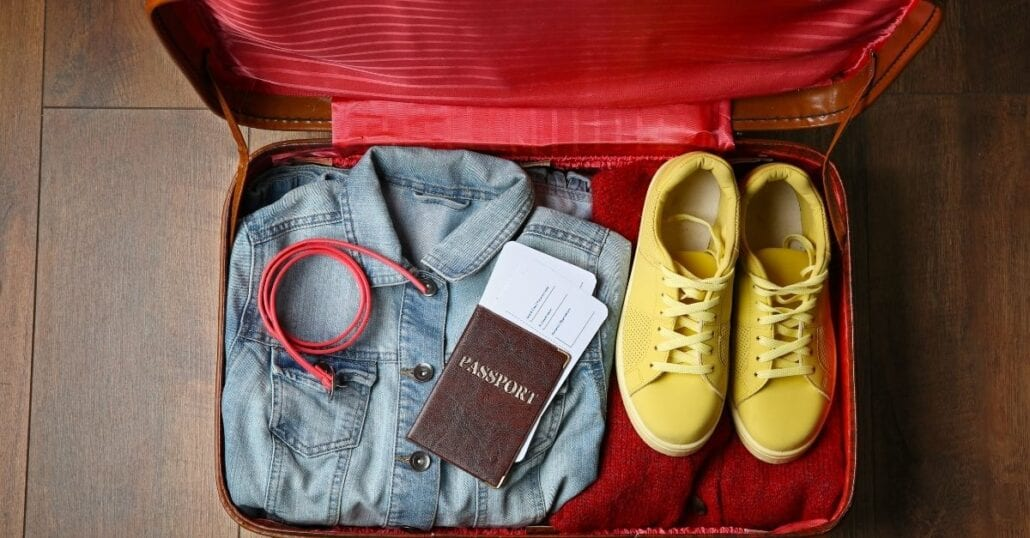 A jacket, an USB cable, a passport, flight tickets and a pair of sneackers inside a red travel suitcase.
