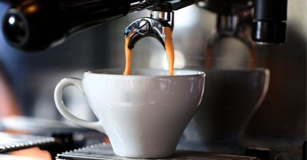 A cup of espresso coffee being made.