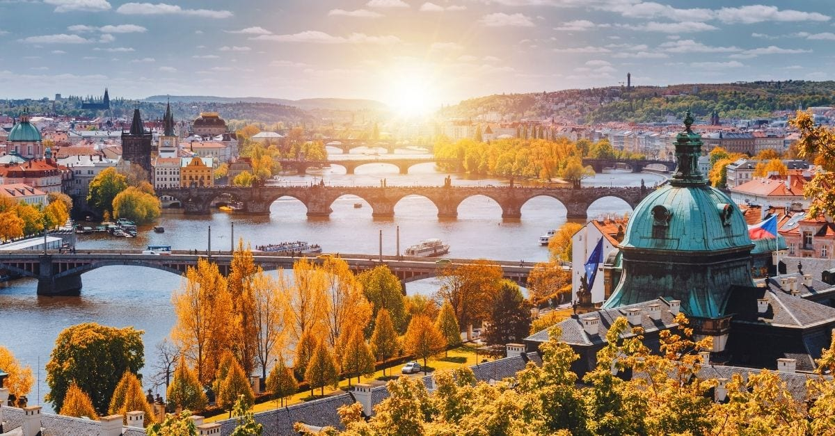 View of the Vltava River, in Prague, crossed by 4 bridges and surrounded by orange and yellow trees.