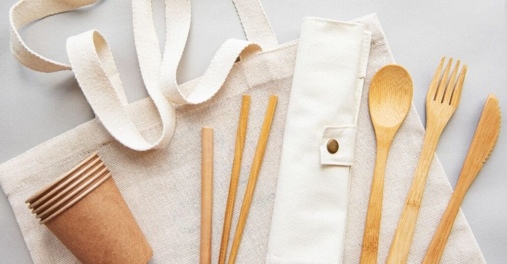 Set of reusable bamboo utensils, such as cups, straws and cutlery.