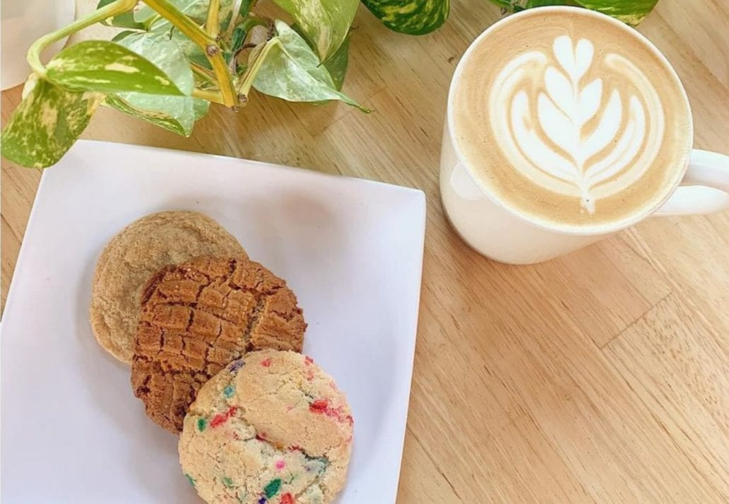 A late and three cookies on top of a table at Rivers and Roads Coffee, Colorado.