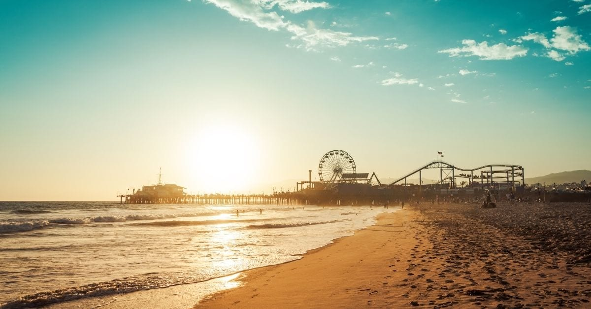 View of the Santa Monica Pier from a beach during the sunset.