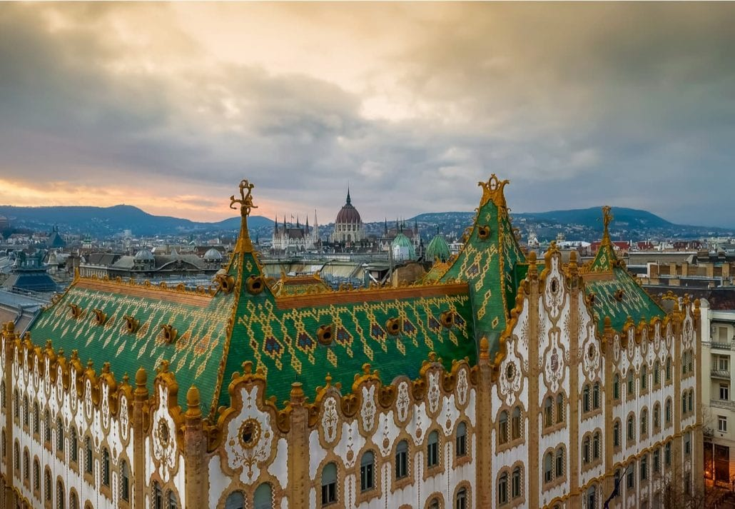 Amazing roof in Budapest, Hungary. State Treasury building with Hungarian Parliament in winter time. All tiles on the roof made from the world famous Zsolnay pyro granite.