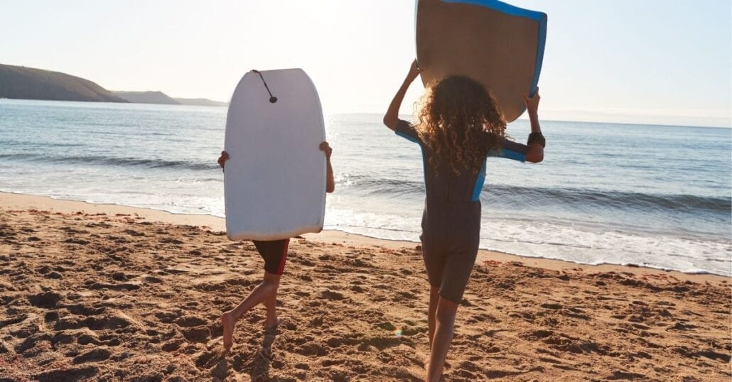 Two kids playing with bodyboards on a sandy beach during a clear afternoon.