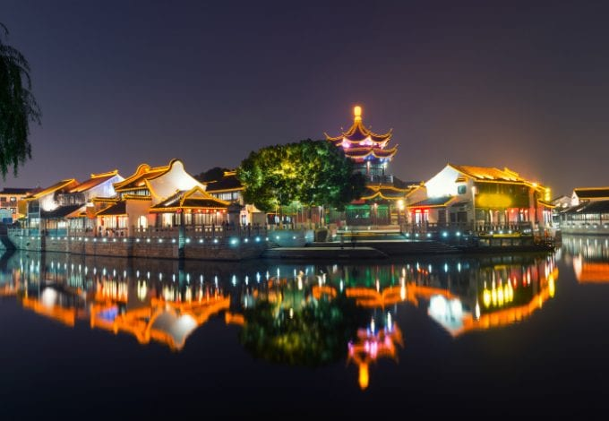 The Grand Canal in Suzhou, China, lined with lighted houses at night.