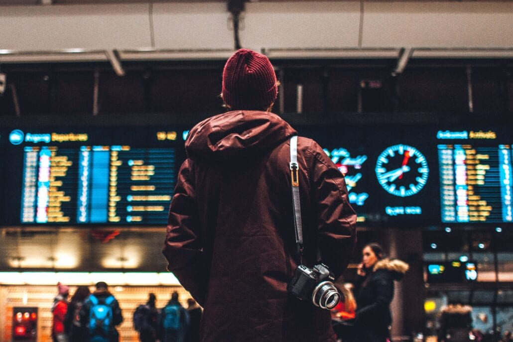 Young traveler checking the timetable at an airport at night.