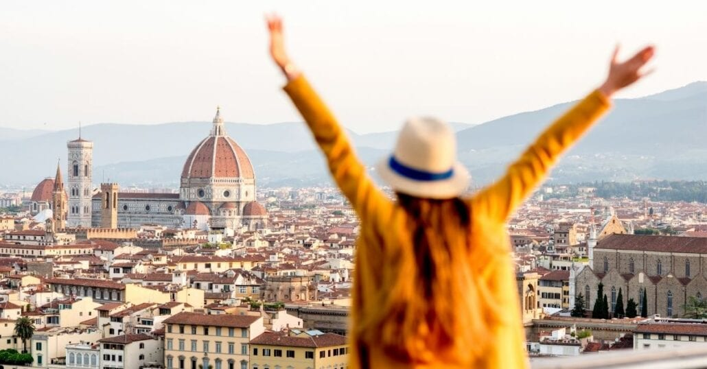 Happy girl with her arms wide open in front of the Florence Cathedral, in Italy.
