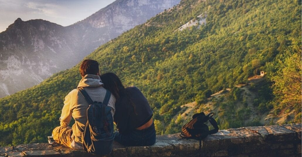 Adventurous-couple sitting and contemplating a a gigantic verdant mountain.