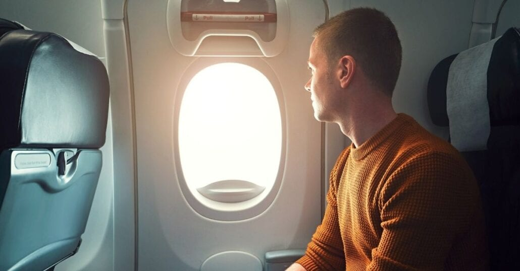 A young man looking through the window on an airplane during the day.