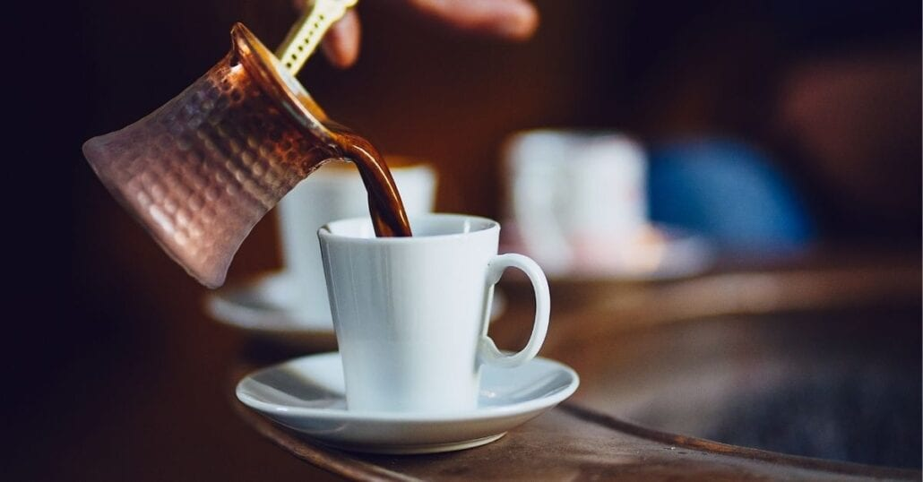 Turkish coffee being poured on a white cup.