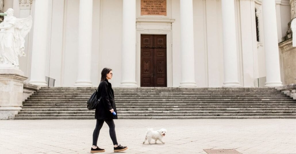 Woman walking with her unleashed white poodle in Vienna, Austria.