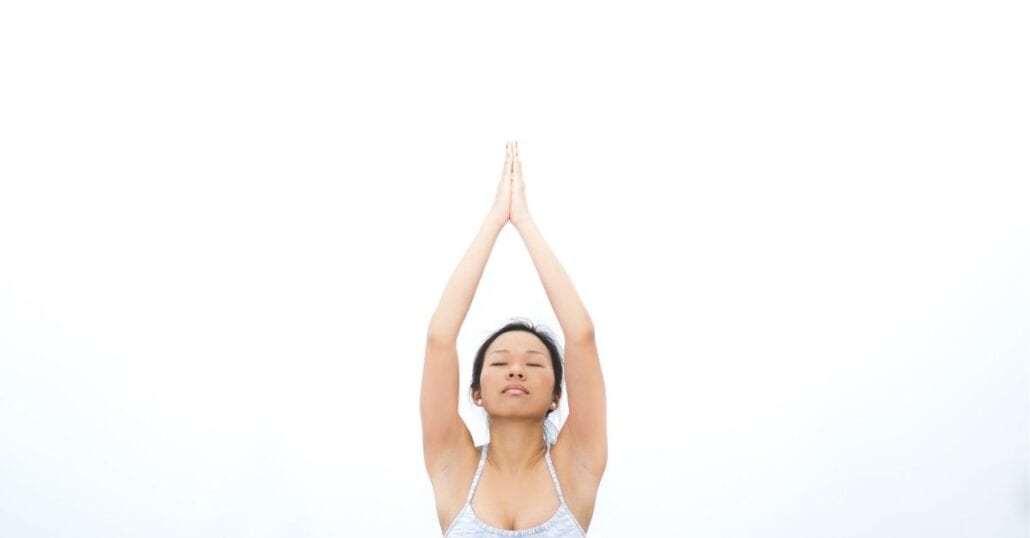 Woman doing yoga with her eyes closed.