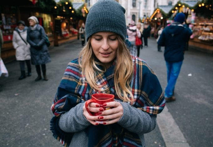 Girl drinking mulled wine at a Christmas market in Vienna, Austria
