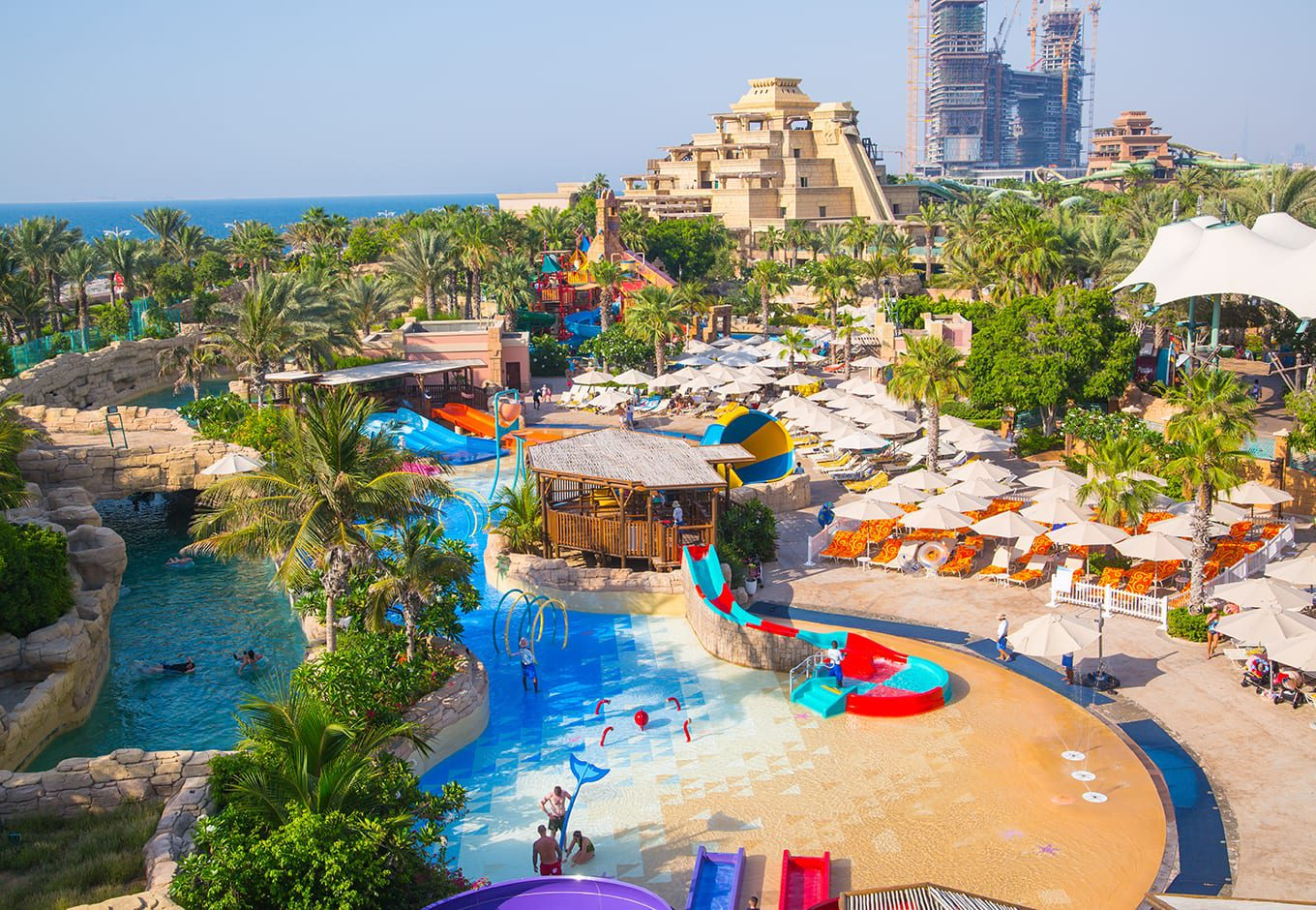 The waterslides and pools surrounded by trees at the Aquaventure, Waterpark, Dubai.