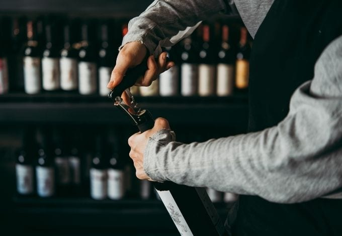 A sommelier opening a bottle of wine at a wine bar.