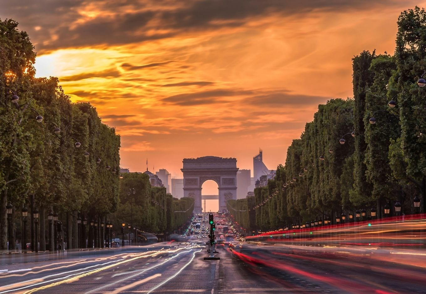 The Arc Du Triomphe at the end of the Champs Élysees Avenue at  sunset in Paris.