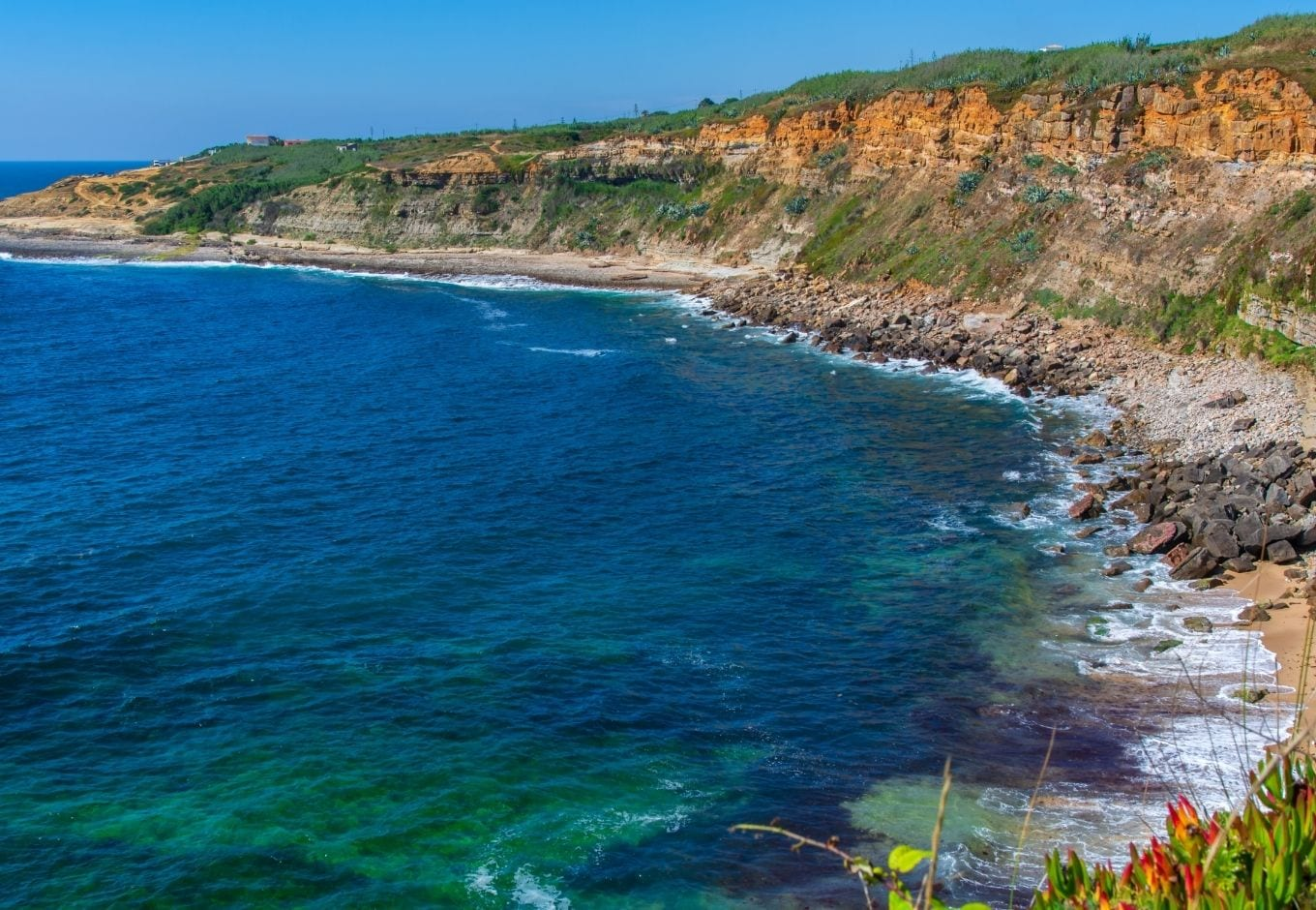 Aerial view of the ocean surrounded by a cliff in Ericeira beach, Portugal.