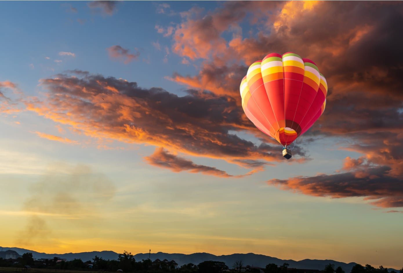 An orange and yellow hot air flying at sunset time. balloon