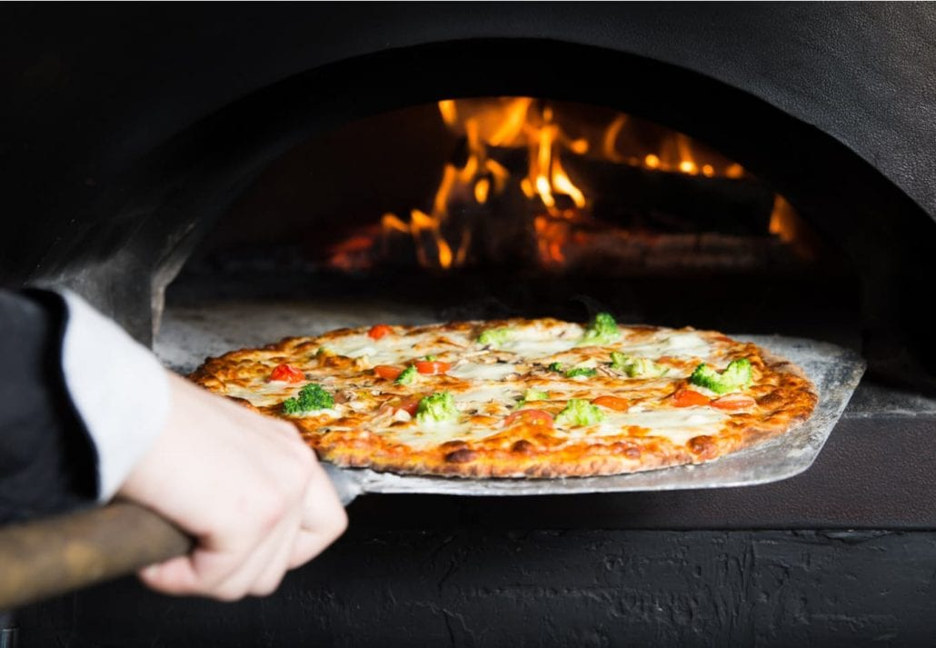 Hot pizza is removing from hot stove where it was baked. Cook using special shovel to removing them. This restaurant have special wood-fired oven.