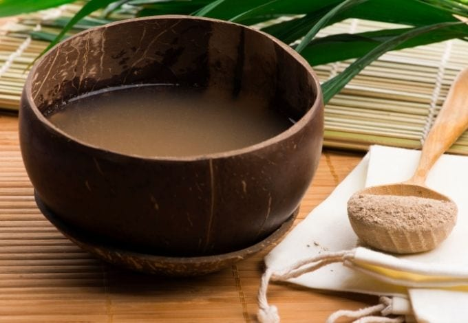 A Kava drink being served on a coconut shell.