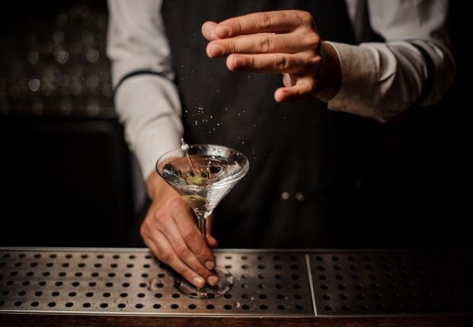 A mixologist seasoning a Martini with a pinch of salt.