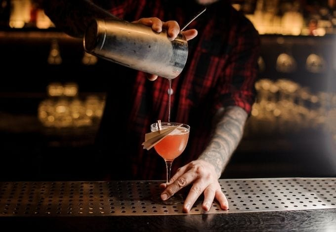 A bartender pouring a drink on a glass.