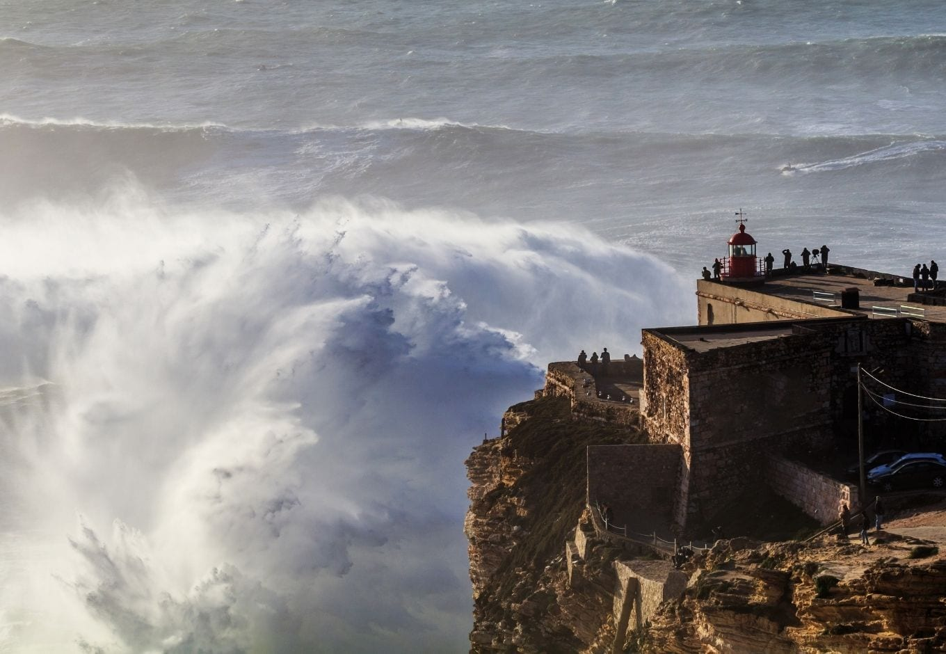 View of a giant Nazaré Wave and the lighthouse at Praia do Norte.
