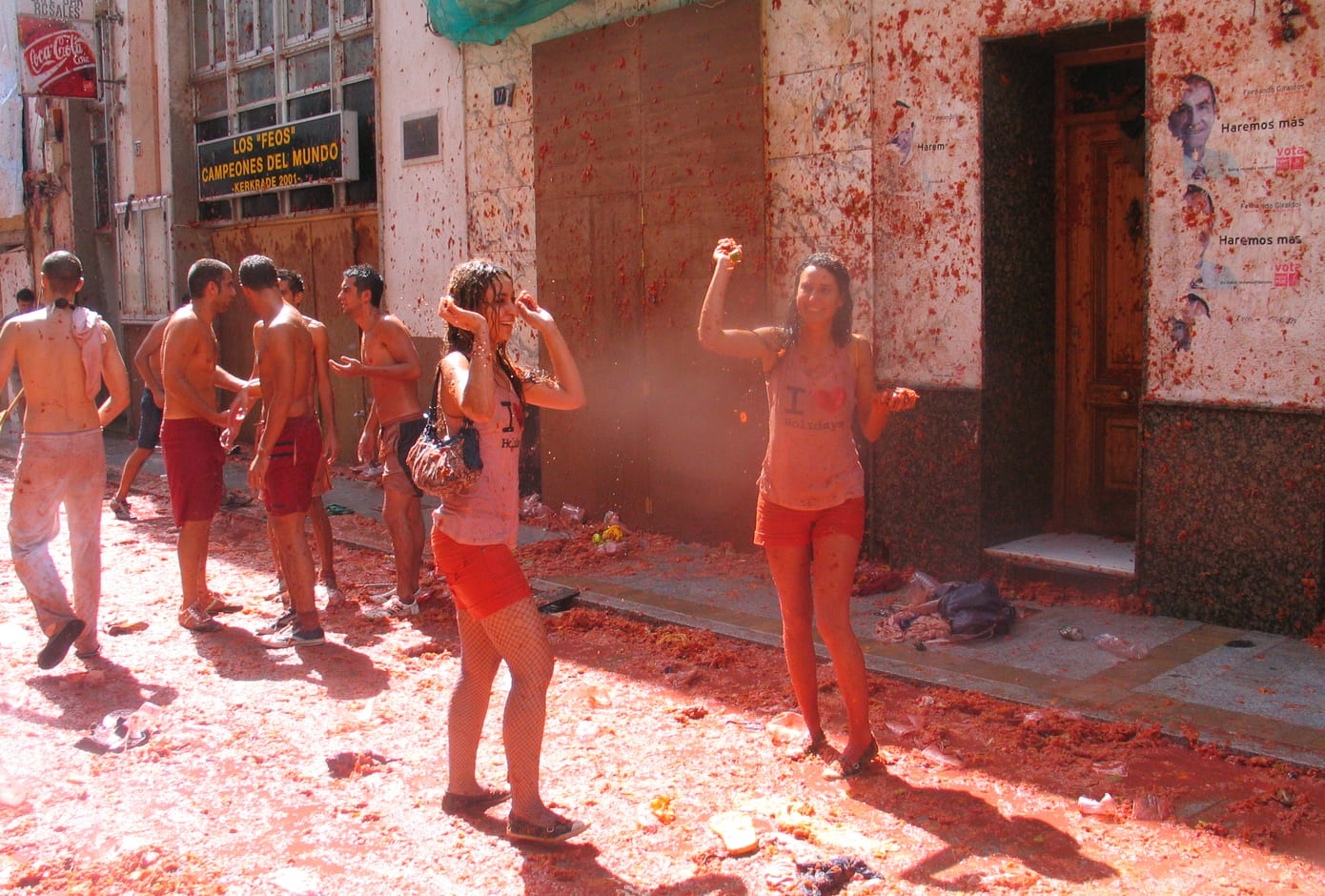 Two girls and a group of male friends covered in tomato juice during La Tomatina, in Spain.