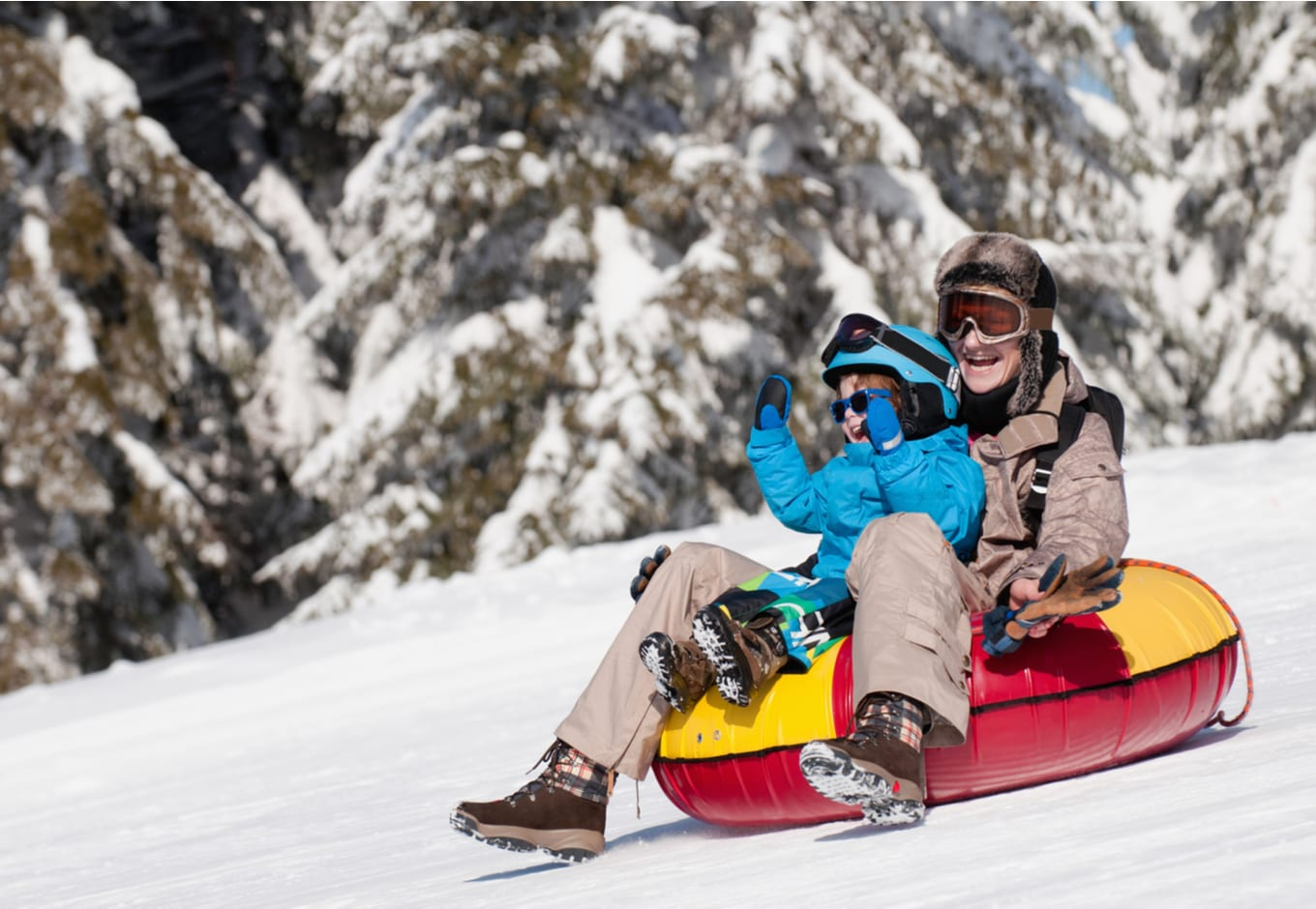 Woman and child sliding down in inflatable snow tube