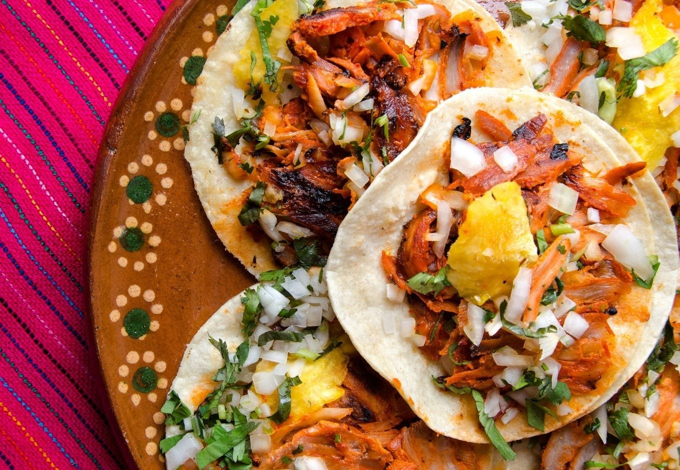 A typical Mexican plate filled with tacos al pastor.