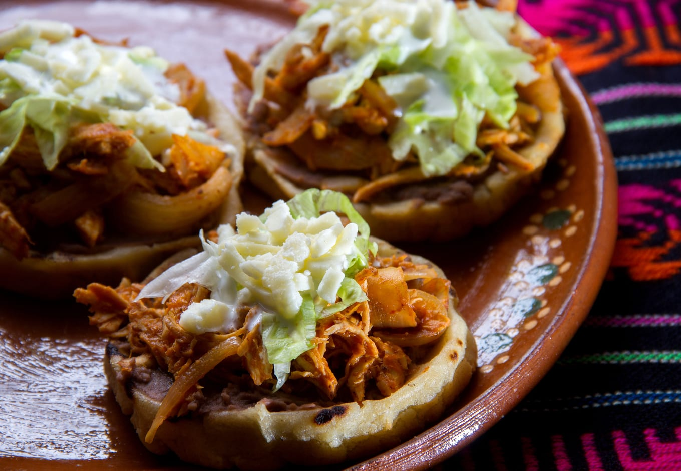 A plate of Tinga Sopes, a traditional Mexican dish.